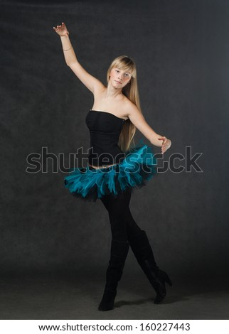 young beautiful dancer with blond hair dancing on a dark studio background - stock photo