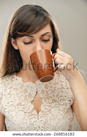 young beautiful dark-haired woman drinking tea from mug, on gray background - stock photo