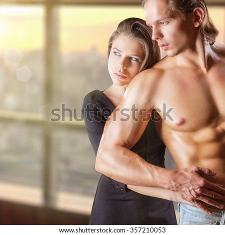 Young beautiful dreaming couple in each other's arms - stock photo