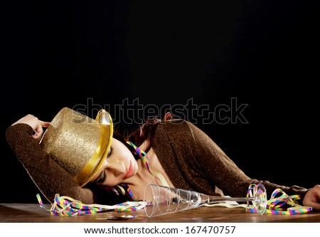 Young beautiful drunk woman sleeping on a table after celebrating new years eve. On black background. - stock photo