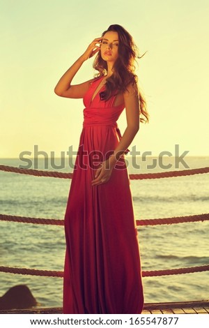 young beautiful elegant woman in pink dress standing near sea - stock photo