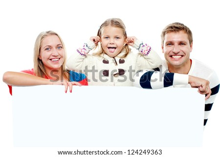 Young beautiful family behind white blank ad board. Cheerful family - stock photo