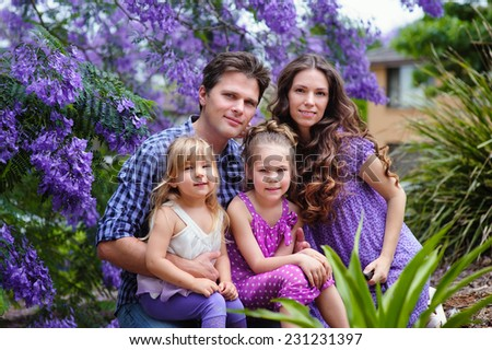 Young beautiful family of mother, father and two little daughters in jacaranda blossom garden - stock photo