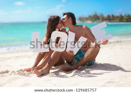"""Young beautiful family sitting on the beach with the word """"Love"""" in their hands  in Mauritius - stock photo"""