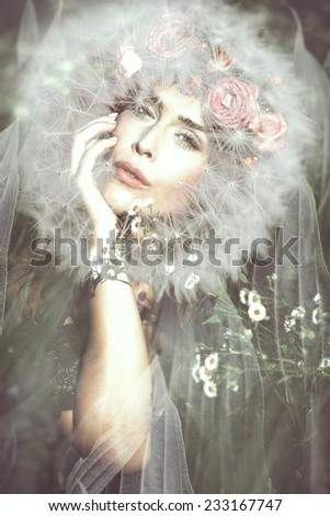 young beautiful  fantasy fairy woman with dandelion around her head on magic meadow - stock photo
