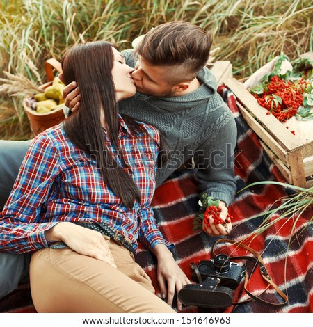 Young beautiful fashion couple in love having fun outdoor in autumn. Stylish handsome man kiss his pretty brunette girlfriend - stock photo