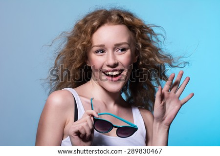 Young beautiful fashion girl smiling with his hand raised and sunglasses in hand. Emotional females with curly hair looks away on a blue background - stock photo