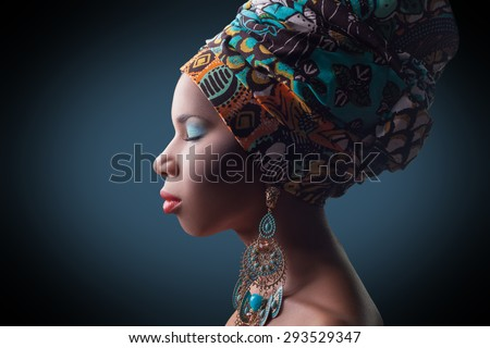 young beautiful fashion model with traditional african style with scarf, earrings and makeup on dark blue background.   Developed from RAW, edited with special care and attention. - stock photo