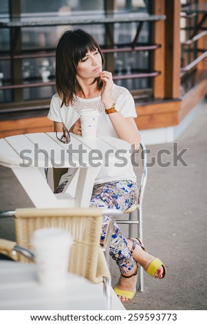 Young beautiful fashion woman sitting in a street cafe drinking coffee - stock photo