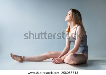 Young beautiful fashionable woman in bathing suit sits on floor - stock photo