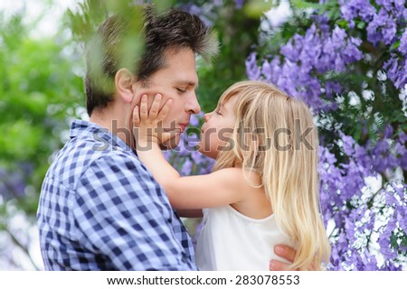 Young beautiful father and his cute daughter love in blooming jacaranda garden - stock photo