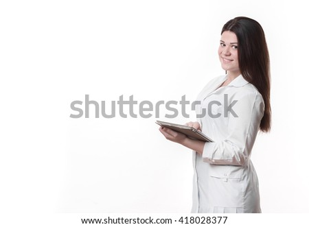 young beautiful female doctor holding clipboard and standing in the edge of the frame, infront of it area for sign or copyspace, isolated over white background - stock photo