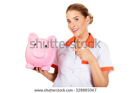 Young beautiful female doctor or nurse holding a piggybank. - stock photo