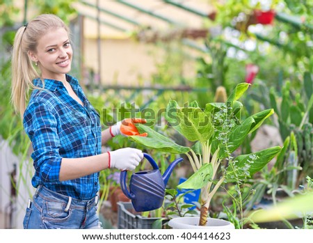 young beautiful female gardener with watering can in greenhouse - stock photo