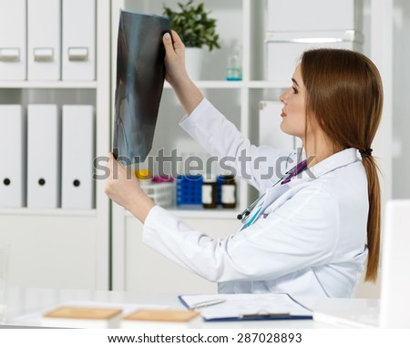 Young beautiful female medical doctor examining x-ray photography of patient to detect problem. Medical concept. Radiologist or traumatologist holding x-ray picture - stock photo