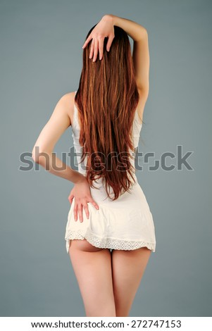 Young beautiful female model in white dress on gray background - stock photo