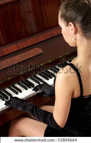 Young beautiful female performer in evening dress playing piano - stock photo