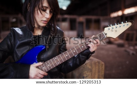 Young beautiful female performer posing with her electric guitar. - stock photo