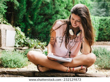 Young beautiful female sitting outside and studying. / Portrait of young woman holding documents on the home garden. - stock photo
