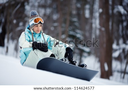 Young beautiful female snowboarder resting on ski slope, she's looking away and smiling - stock photo
