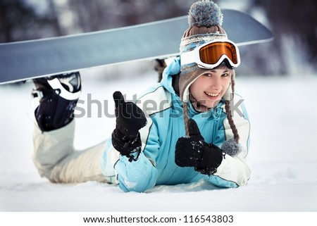 Young beautiful female snowboarder resting on ski slope, she's lying on front, showing thumbs up and smiling, close up - stock photo