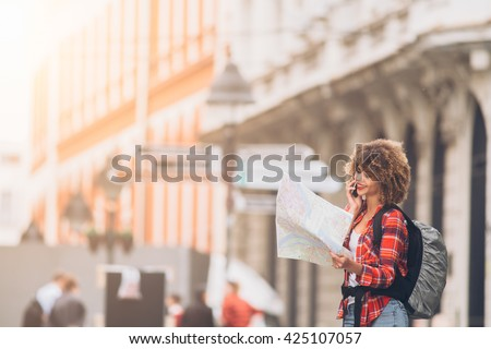 Young beautiful female traveler looking at the map  - stock photo