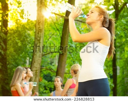 Young beautiful fit woman standing in nature. Other women in background. - stock photo