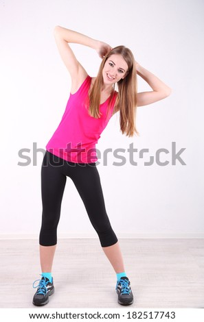 Young beautiful fitness girl exercising in gym - stock photo