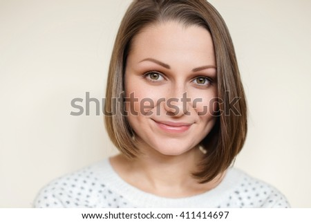 Young beautiful freckled Caucasian brunette with bob haircut, hazel eyes, neutral makeup, wearing crew / round neck sweater, looking at camera smiling. Off white background - stock photo