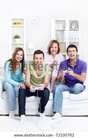 Young beautiful friends play video games at home - stock photo
