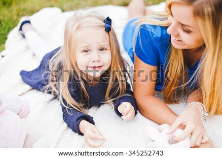 Young beautiful funny girl and her mom on picnic in park at sunny summer day relaxing outdoors. Emotion expressions on kid face. Little kid fools at camera - stock photo