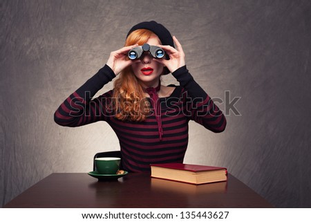 young beautiful ginger woman looking at you with her binoculars on grunge background - stock photo