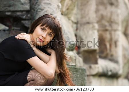 young beautiful girl against an impressive stone wall - stock photo