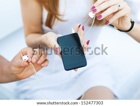 Young beautiful girl and her mother holding a MP3 player and headphones. - stock photo