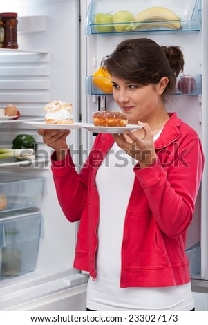 Young beautiful girl and tough choice between two cakes - stock photo