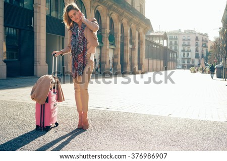 young beautiful girl arrived at a business meeting in a European city.young beautiful well-dressed businesswoman with a pink suitcase waiting for the business partner. - stock photo