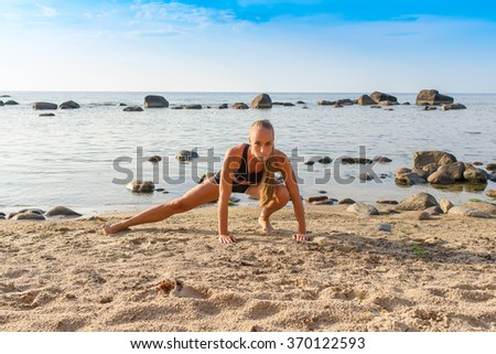 Young beautiful girl athlete on the beach in summer - stock photo