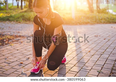 Young beautiful girl athlete with armband and earphones listening to music and tying laces during training in park with sunset and sunbeam on background. Copy space. Bright and warm photo - stock photo