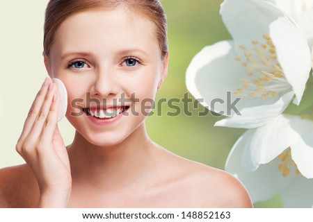 Young beautiful girl cleans the eye make-up - stock photo