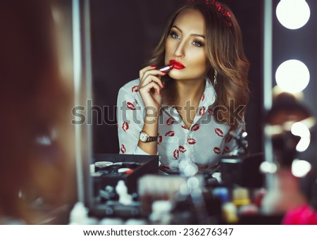 Young beautiful girl doing makeup with red lipstick - stock photo