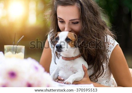 Young, beautiful girl has received a long-awaited gift-dog breed Jack Russell Terrier. She  happiness and love  animals.Girl sitting at a restaurant or cafe table outdoors. Flowers on the background. - stock photo