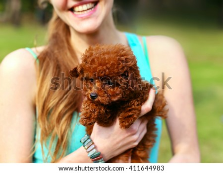 Young beautiful girl holding a cute brown puppy. The girl smiles.  - stock photo