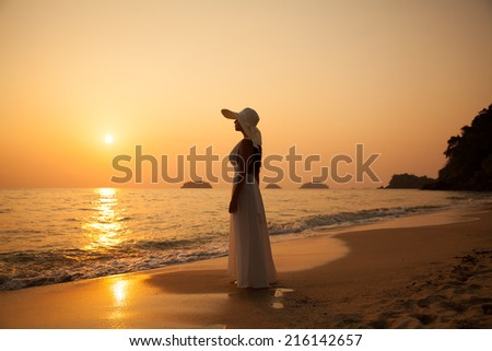 Young beautiful girl in a white dress and straw hat on a tropical beach at sunset. Summer vacation concept. - stock photo