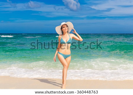 Young beautiful girl in bikini and straw white hat on the beach of a tropical island. Summer vacation concept. - stock photo