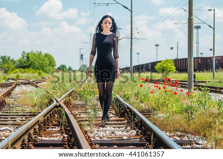 Young beautiful girl in black dress and nylons walking down rail tracks, cargo wagons and poppies in background - stock photo