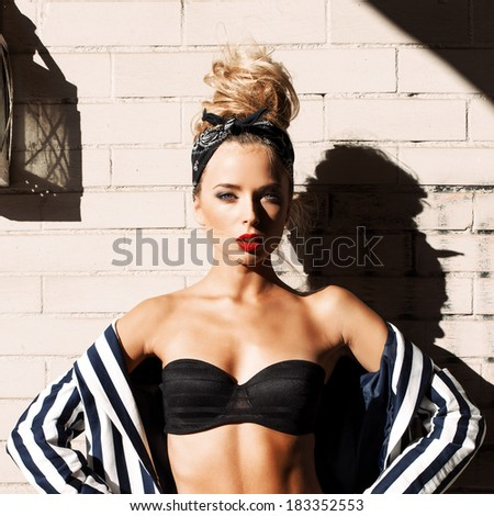 young beautiful girl in fashion style posing against white brick wall looks into the camera - stock photo