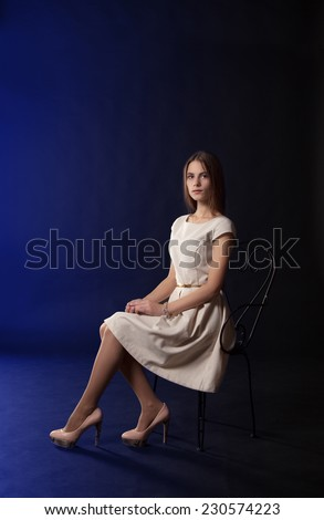 young beautiful girl in light dress sitting on a chair - stock photo