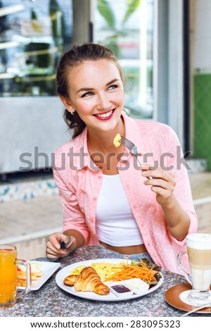 Young, beautiful girl in the breakfast cafe. She ordered scrambled eggs, croissant, latte and orange juice. Looking nice and cute and fresh. - stock photo