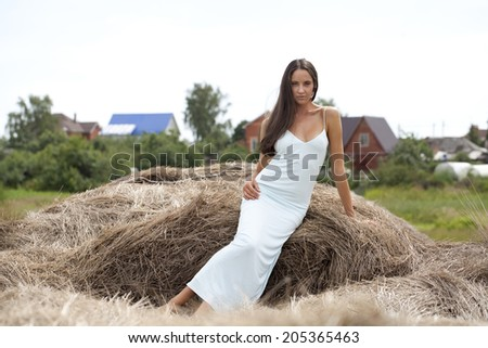Young beautiful girl in the hayloft in the village - stock photo