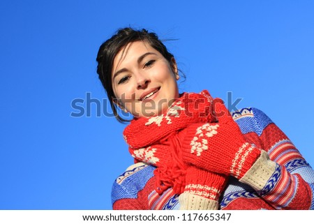 Young, beautiful girl in winter clothing looking into a camera and smiling - stock photo